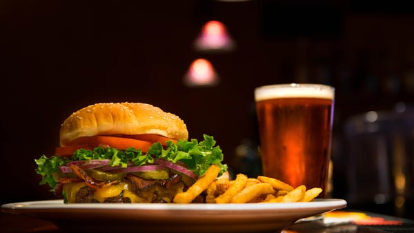 hamburger and fries on a plate, with a beer