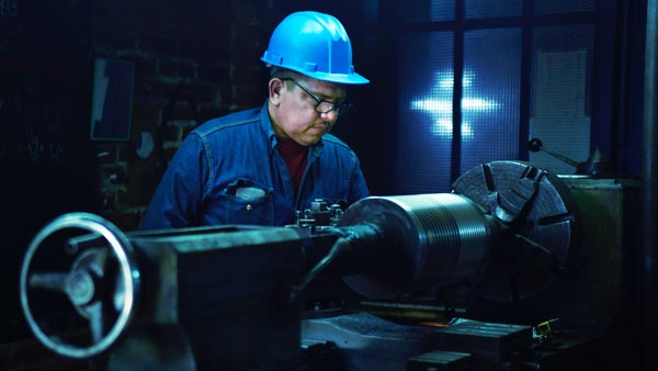 person using heavy metal lathe to manufacture something